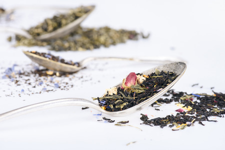 close-up view of aromatic organic herbal tea and spoons on grey