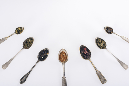 top view of assorted organic herbal tea in spoons isolated on grey