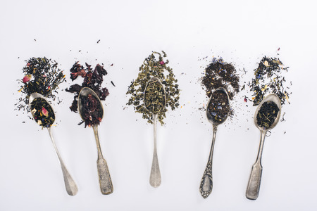 top view of assorted aromatic organic herbal tea in spoons on grey