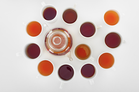 top view of various healthy herbal tea in cups and teapot on grey