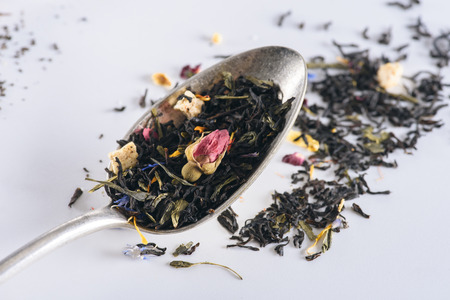 close-up view of healthy herbal tea in spoon on grey