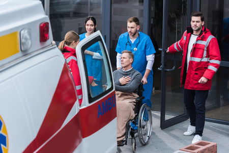 doctors helping man on wheelchair get to ambulance Stock Photo