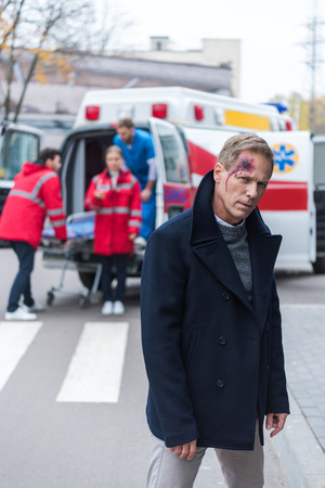 injured man with wound on head standing and looking at camera Stockfoto