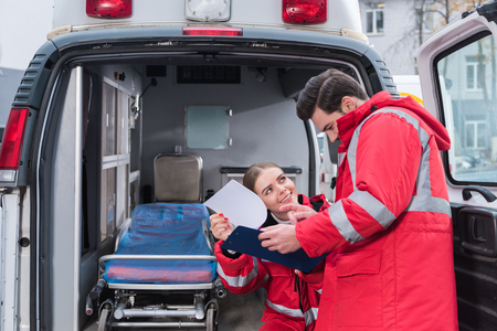 happy male and female paramedics reading documents in front of ambulance
