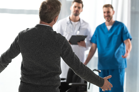 healthy patient going with open arms to smiling doctors