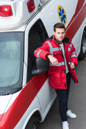 serious young male paramedic standing and leaning on ambulance