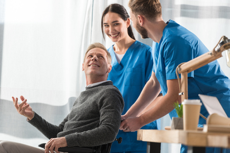 smiling doctors and patient on wheelchair talking in the hospital