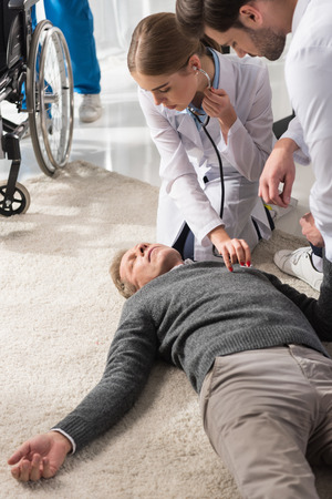 female doctor checking unconscious middle aged man palpitation with stethoscope