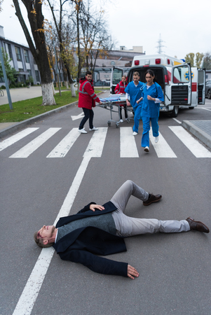 paramedics running to help injured man lying on a street Archivio Fotografico