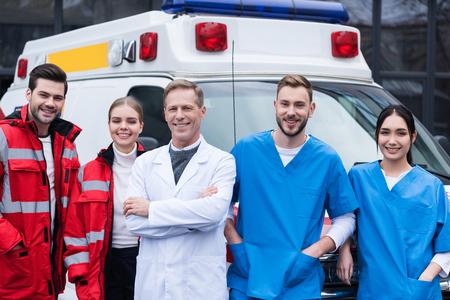 glückliches Arbeitsteam der Krankenwagenärzte, das vor Auto steht