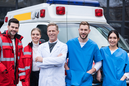 happy ambulance doctors working team standing in front of car Stock Photo