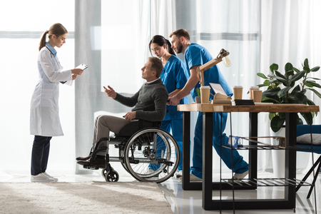 female doctor talking with middle aged patient on wheelchair