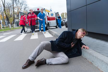 injured man with wound on head lying on a street 版權商用圖片