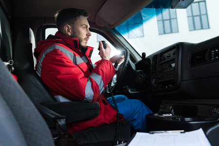 young handsome male paramedic talking by portable radio Standard-Bild