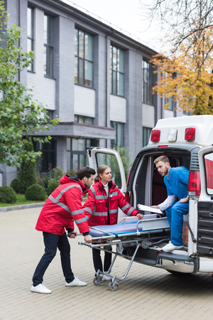 paramedics moving ambulance stretcher into car Stok Fotoğraf