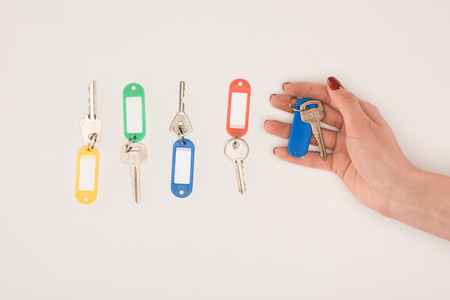 top view of hand holding key beside set of keys with colorful labels isolated on white Stock Photo