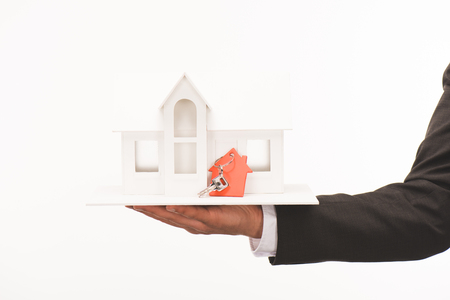 cropped image of hand holding maquette of house with key isolated on white Stock Photo