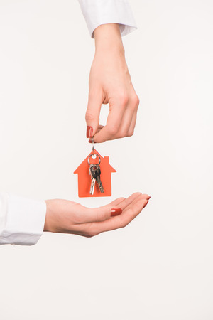 cropped image of female hands holding key from house isolated on white Stock Photo