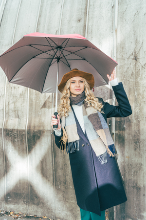 beautiful young woman in autumn outfit standing with umbrella outside