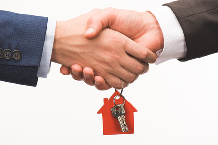 cropped image of shaking hands with key from house isolated on white Stock Photo