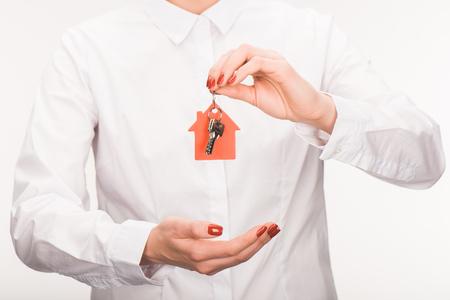 cropped image of female holding key from house isolated on white