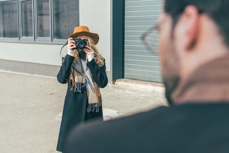 El enfoque selectivo de la elegante joven con cámara fotografiando novio fuera