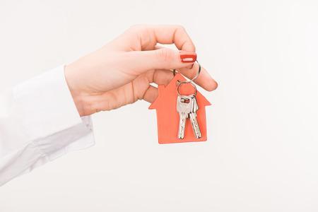 cropped image of female hand holding key from house isolated on white Stock Photo