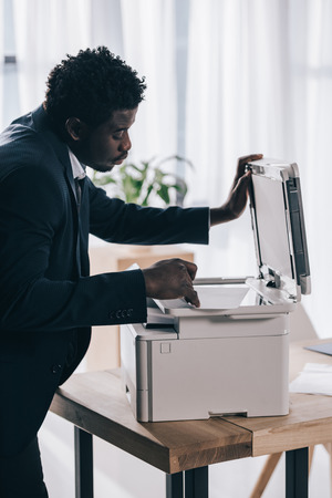 african american manager using copier at office