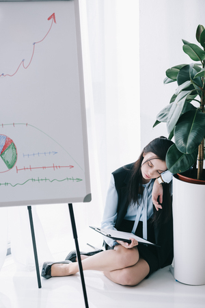 businesswoman sleeping at office while leaning on flower pot