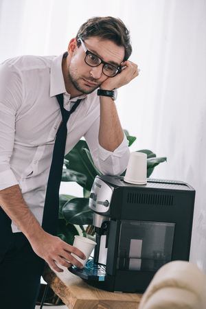 bored overworked businessman pouring coffee from office machine Stock Photo