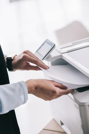 cropped shot of woman in formal wear using copier