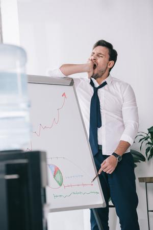 yawning sleepy businessman making presentation at office