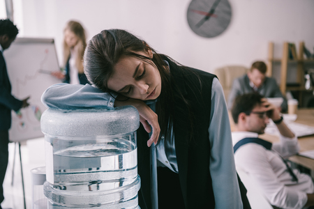 exhausted zombie like manager leaning on water dispenser at office