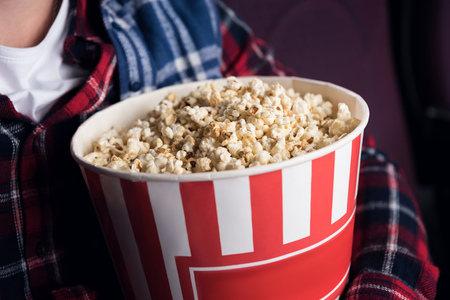 cropped view of man holding big basket of popcorn in movie theater