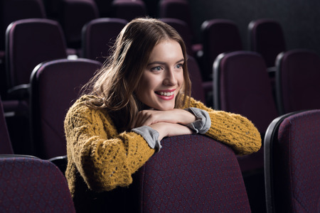 young smiling girl watching film in cinema Banco de Imagens
