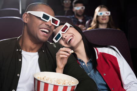 happy interracial couple in 3d glasses eaying popcorn and watching movie in cinema