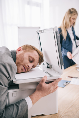 overworked young businessman sleeping with head on copier at office Stock Photo