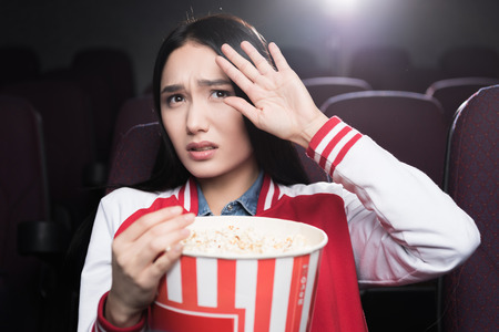 frightened asian girl eating popcorn and watching movie in cinema Banco de Imagens