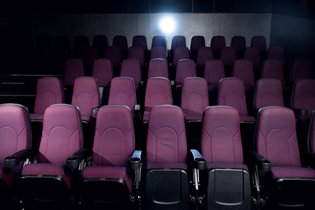 red seats in empty dark movie theater with back light Stock fotó