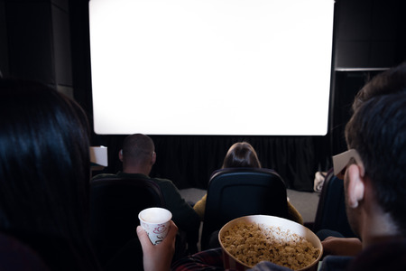back view of friends with popcorn and drink sitting in cinema with white blank screen