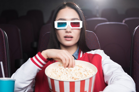 young asian girl in 3d glasses with big basket of popcorn watching movie in cinema