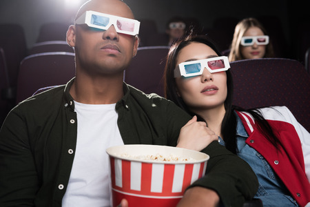 young interracial couple in 3d glasses with popcorn watching movie in cinema Archivio Fotografico