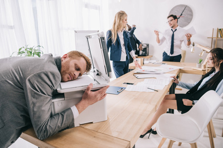 exhausted zombie like businessman sleeping on copier while his colleagues having conversation at office