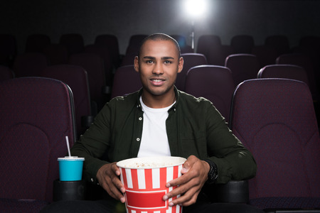 african american man with popcorn and soda watching film in movie theater