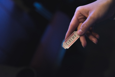 cropped view of woman holding cinema ticket in hand