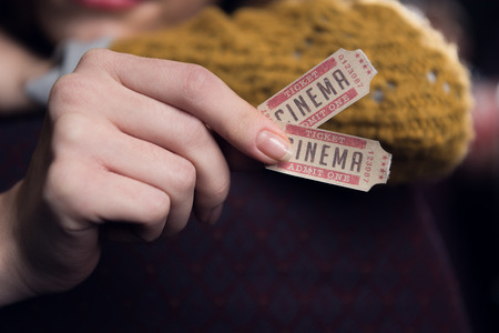 cropped view of woman holding two cinema tickets