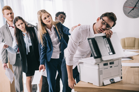 exhausted businessman sleeping on copier while his colleagues standing in queue behind him Stock Photo