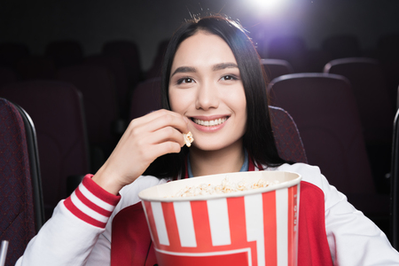 young asian girl eating popcorn and watching movie in cinema