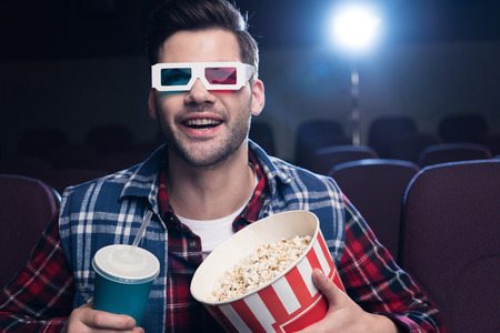 excited man in 3d glasses with popcorn and soda watching movie in cinema