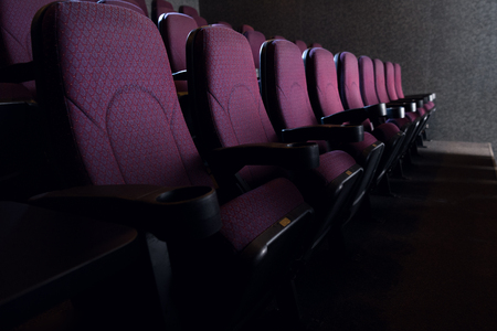 rows of red seats in empty dark cinema